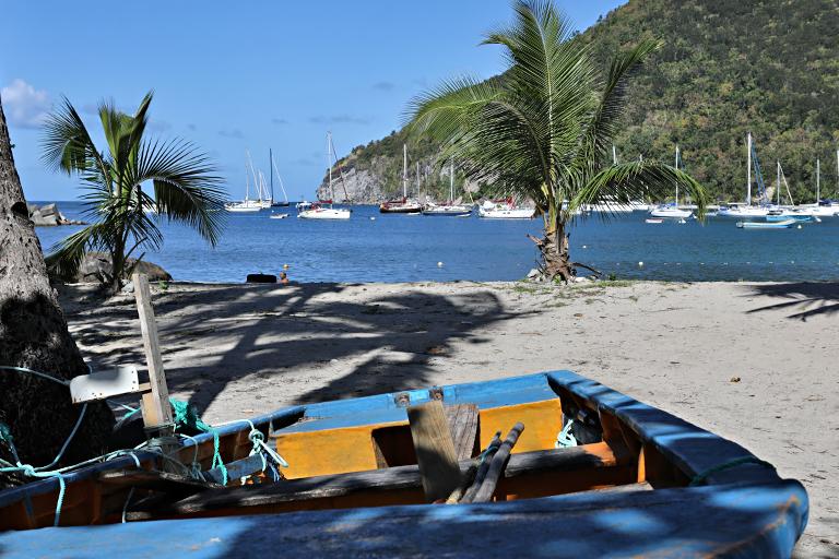 kleines Boot am Strand vor dem Hafen von Deshaies auf Guadeloupe