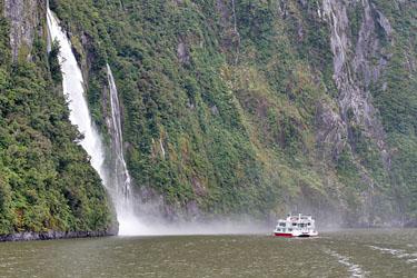 schiff unter wasserfall, milford sound, neuseeland