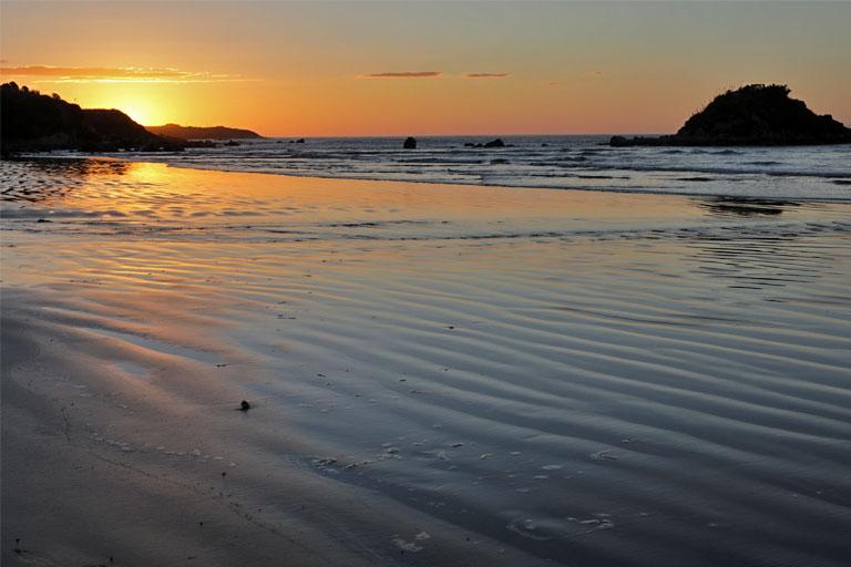 sonnenuntergang am monkey island beach, neuseeland